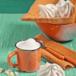Side view of meringues and orange cup — Stock Photo