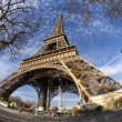 Eiffel Tower in Paris with green grass, blue sky and white clouds - Stock Photo