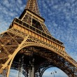 Eiffel Tower in Paris with green grass, blue sky and white clouds — Stock Photo