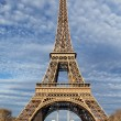 Eiffel Tower in Paris with green grass, blue sky and white clouds — Stock Photo #18727877