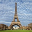 Eiffel Tower in Paris with green grass, blue sky and white clouds — Stock Photo #18728079