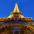 Illuminated Eiffel Tower from Paris, France in the night - Stock Photo