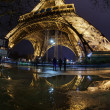 Illuminated Eiffel Tower from Paris, France in the night with water reflaction - Stock Photo