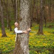 A happy man hugging a tree in forest - Stock Photo