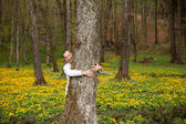 A happy man hugging a tree in forest — Stock Photo