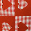 Foto Stock: Checkered background in red tones decorated with heart