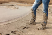 Muddy and dirty Hiking Boots and blue jeans — Stock Photo