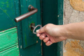 Hand open old door with old key — Stock Photo