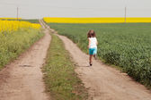 Kid having happy time running on road in the field of rapeseed — Stock Photo