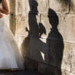 Bride and groom near to wall with shadow — Stock Photo