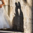 Bride and groom kissin near to wall with shadow — Stock Photo