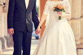 Wedding couple holding hands — Stock Photo