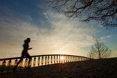 日の出、橋の上で実行している女の子のシルエット — ストック写真