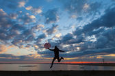 Happy woman silhouette with umbrella jumping at sunrise — Stock Photo