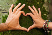 Heart hand on tree with moss by man and woman, loving the nature — Stock Photo