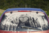 Dirty rear window of the car and inscription of a heart — Stock Photo