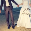 Wedding couple holding on trash the dress with dirty dress — Stock Photo #42649407