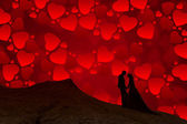 Silhouette of couple with red sky full of hearts — Stock Photo