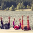 Color image of three children siting on pontoon on lake — Stock Photo #42651467