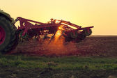 Tractor on sunset doing agriculture — Stock Photo