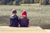 Color image of two children siting on pontoon on lake — Stock Photo