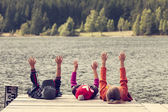 Color image of three children siting on pontoon on lake — Stock Photo