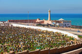 Muslim cemetery - with the lighthouse on sea coast background - — Stock Photo