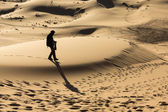 Man walking on dunes in desert — Stock Photo