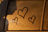 Hearts draw on water of window of a car with shadow of woman — Stock Photo