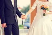 Wedding couple holding hands with flower holding — Stock Photo