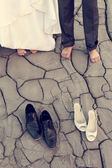 Legs of wedding couple in dirty shoes — Stock Photo