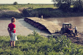 Child looking at bridge over river with tractor in background — Stockfoto