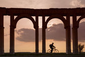 Silhouette of bike under columns in sunset — Stock Photo