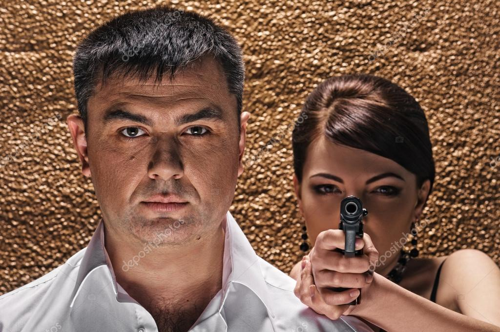 Woman with pistol and man about texture wall — Stock Photo #16772967