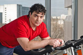 Young man on exercise bicycle — Stock Photo