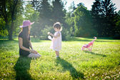 A little girl with mom in a summer park — Foto de Stock