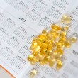 Colored yellow pills on the background Datebook — Stock Photo
