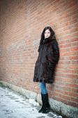 Menina bonita no inverno contra uma parede de tijolos — Fotografia Stock