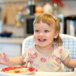 Beautiful little girl laughing and eating at the table. — Stock Photo