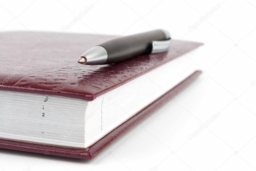 Black ballpoint pen lying on the leather cover diary  Stock Photo #15863081