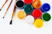 Jars with colored gouache and paint brushes. — Stock Photo