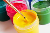 Colorful paint containers and brush — Stock Photo