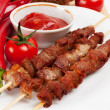 Shish kebab on bamboo sticks on white plate - Stock Photo