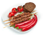 Shashlik on a plate with cherry tomatoes. — Stock Photo