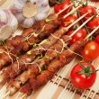 Pork skewers with cherry tomatoes and garlic - Stock Photo