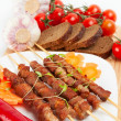 Shish kebab with herbs on a white plate — Stock Photo