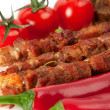 Shish kebab on bamboo sticks with cherry tomatoes — Stock Photo #25120595