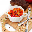 Letcho, tomatoes, black bread on a cutting board — Stock Photo