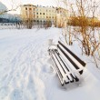 An empty bench in the snow-covered city park. — Stock Photo