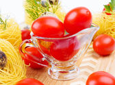 Glass Gravy boat with cherry tomatoes. — Stock Photo